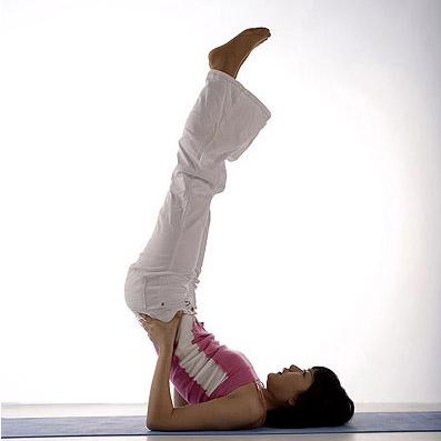 performing the sarvangasana yoga pose aka shoulder stand